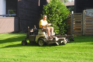 Man riding mower and cutting lawn